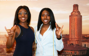 Two black female UT students holding Hook 'Em sing with UT Tower on the background